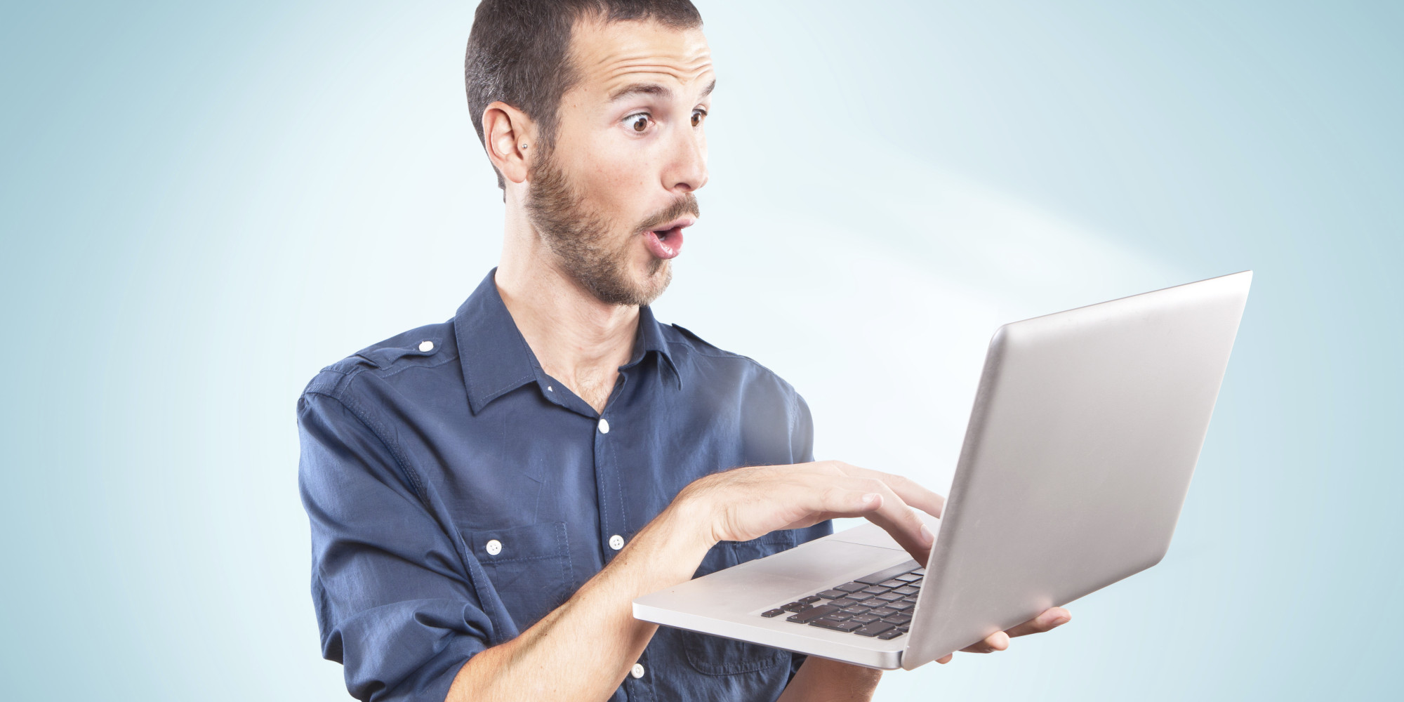 Young man surprised holding a laptop